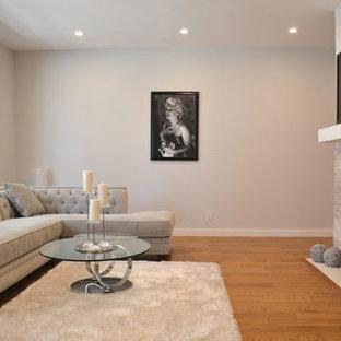 Imagen de salón abierto, moderno, pequeño, con paredes grises, suelo de madera en tonos medios, chimenea tradicional, marco de chimenea de baldosas y/o azulejos y televisor colgado en la pared