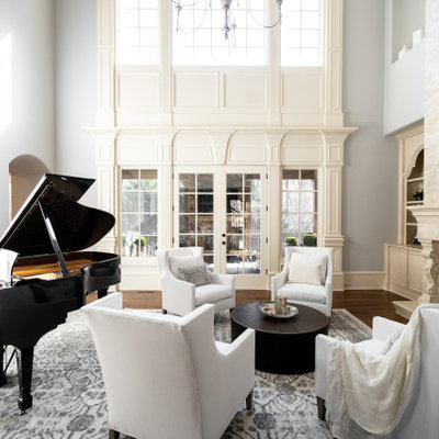 Example of a classic enclosed medium tone wood floor and brown floor living room design in Atlanta with a music area, brown walls, a standard fireplace and no tv