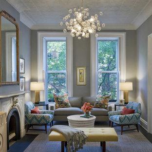 ニューヨークの中サイズのトランジショナルスタイルのおしゃれなリビング (フォーマル、グレーの壁、標準型暖炉、テレビなし、石材の暖炉まわり、茶色い床) の写真