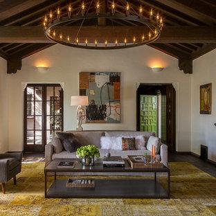 Exemple d'un très grand salon avec une bibliothèque ou un coin lecture méditerranéen fermé avec un mur blanc, un sol en bois foncé et aucun téléviseur.