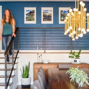 デンバーの中くらいのビーチスタイルのおしゃれなLDK (ライブラリー、白い壁、無垢フローリング、標準型暖炉、積石の暖炉まわり、茶色い床、三角天井) の写真