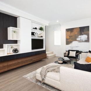 Inredning av ett modernt stort allrum med öppen planlösning, med vita väggar, laminatgolv, brunt golv och en inbyggd mediavägg