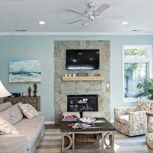 他の地域の中サイズのビーチスタイルのおしゃれなLDK (青い壁、淡色無垢フローリング、標準型暖炉、石材の暖炉まわり、壁掛け型テレビ) の写真