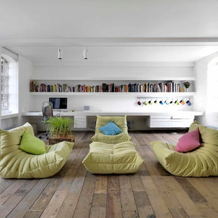 Design ideas for an industrial open plan living room in London with a reading nook, white walls and medium hardwood flooring.
