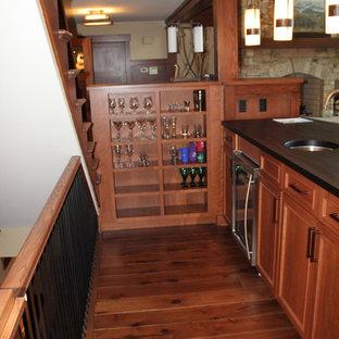 アルバカーキのおしゃれなリビングのホームバー (濃色無垢フローリング、標準型暖炉、石材の暖炉まわり) の写真