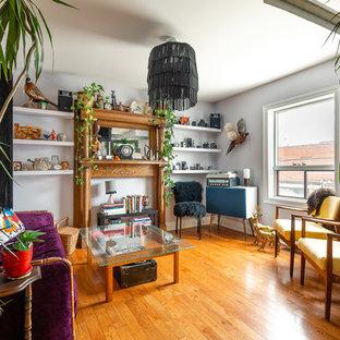 Modelo de salón cerrado, ecléctico, pequeño, sin televisor, con paredes púrpuras, suelo de madera en tonos medios, chimenea tradicional, marco de chimenea de madera y suelo marrón