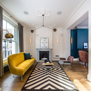 Inspiration for a large contemporary enclosed living room in London with white walls, medium hardwood flooring, a standard fireplace, a stone fireplace surround and no tv.