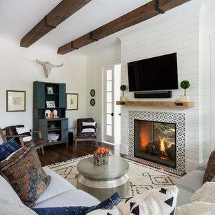 Inspiration för maritima vardagsrum, med vita väggar, mörkt trägolv, en dubbelsidig öppen spis, en spiselkrans i trä, en väggmonterad TV och brunt golv