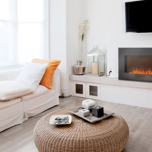 Immagine di un soggiorno minimal di medie dimensioni con pareti beige, camino sospeso e pavimento beige