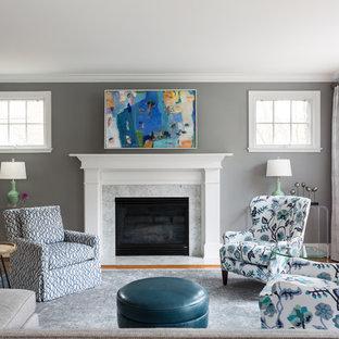 Immagine di un soggiorno tradizionale chiuso con sala formale, pareti grigie, pavimento in legno massello medio, camino classico, cornice del camino in pietra e pavimento arancione