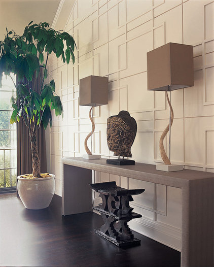 living space with off-white textured walls, off-white credenza with eclectic art sculptures, modern art deco lamps, artificial tree by betsy burnham
