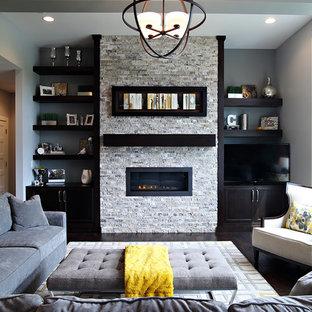 Modelo de salón para visitas clásico renovado con paredes grises, suelo de madera oscura, chimenea lineal, marco de chimenea de piedra y televisor independiente