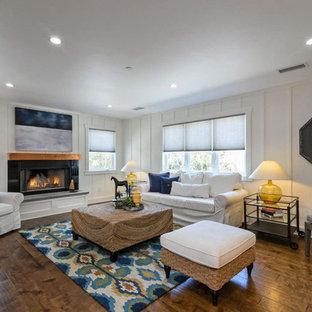 他の地域の中サイズのビーチスタイルのおしゃれなLDK (白い壁、無垢フローリング、標準型暖炉、コンクリートの暖炉まわり、壁掛け型テレビ、茶色い床) の写真
