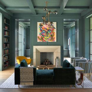 Exempel på ett mellanstort eklektiskt allrum med öppen planlösning, med ett bibliotek, gröna väggar, mellanmörkt trägolv, en standard öppen spis, brunt golv och en spiselkrans i sten