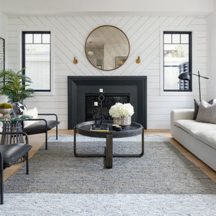 ロサンゼルスの広いトランジショナルスタイルのおしゃれなLDK (標準型暖炉、フォーマル、白い壁、金属の暖炉まわり、テレビなし、ベージュの床、塗装板張りの壁) の写真