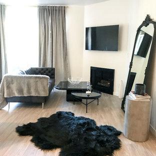 Modelo de salón cerrado, contemporáneo, pequeño, con paredes blancas, suelo de madera clara, chimenea de esquina, marco de chimenea de metal, televisor colgado en la pared y suelo marrón