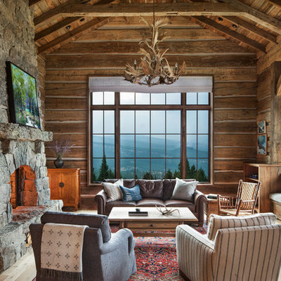 Large mountain style formal light wood floor living room photo in Other with brown walls, a standard fireplace and a stone fireplace