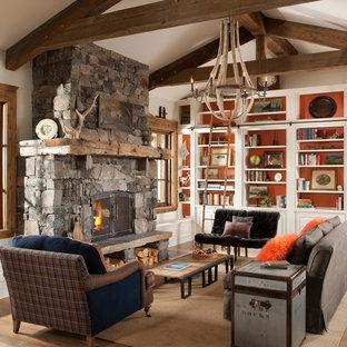 Foto di un soggiorno rustico con libreria, pareti bianche, pavimento in legno massello medio, camino classico e cornice del camino in pietra