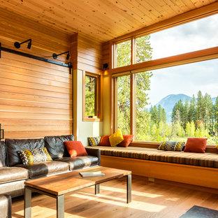 Immagine di un soggiorno rustico aperto e di medie dimensioni con libreria, stufa a legna, cornice del camino in metallo, pareti marroni, parquet chiaro e pavimento beige