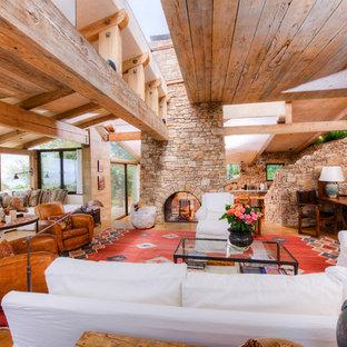 サンフランシスコの巨大な地中海スタイルのおしゃれなLDK (フォーマル、茶色い壁、コンクリートの床、両方向型暖炉、石材の暖炉まわり) の写真