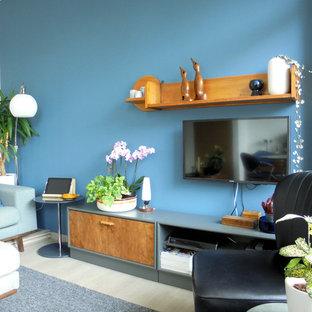 Modelo de salón abierto, vintage, pequeño, con paredes azules y televisor colgado en la pared