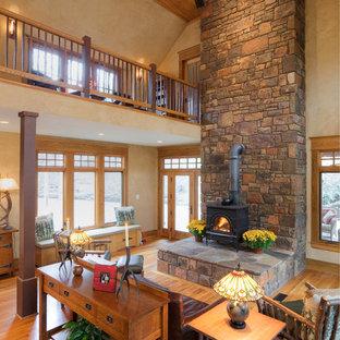 Ispirazione per un soggiorno classico di medie dimensioni e aperto con sala formale, pareti beige, parquet chiaro, stufa a legna e cornice del camino in metallo