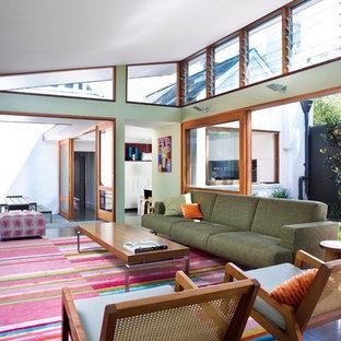 Foto på ett mellanstort funkis allrum med öppen planlösning, med gröna väggar, skiffergolv, en väggmonterad TV och svart golv
