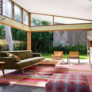 Bild på ett mellanstort funkis allrum med öppen planlösning, med gröna väggar, skiffergolv, en väggmonterad TV och svart golv