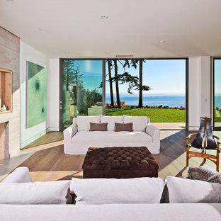 ロサンゼルスの大きいビーチスタイルのおしゃれなLDK (フォーマル、白い壁、淡色無垢フローリング、標準型暖炉、コンクリートの暖炉まわり、テレビなし、茶色い床) の写真