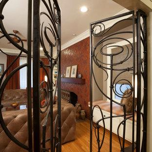 Diseño de salón cerrado, de estilo americano, sin televisor, con parades naranjas, suelo de madera clara, chimenea tradicional y marco de chimenea de baldosas y/o azulejos