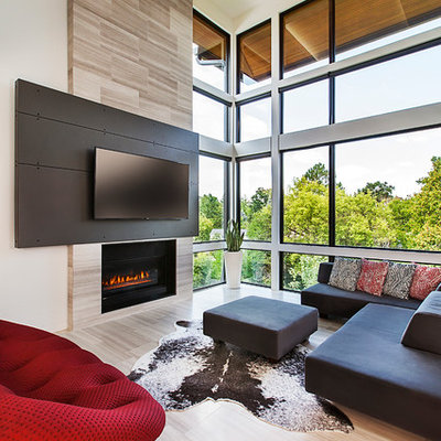 Inspiration for a mid-sized contemporary open concept light wood floor living room remodel in Detroit with a standard fireplace, a wall-mounted tv and beige walls