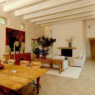 アルバカーキの広いサンタフェスタイルのおしゃれなLDK (フォーマル、ベージュの壁、レンガの床、標準型暖炉、漆喰の暖炉まわり、テレビなし、茶色い床) の写真