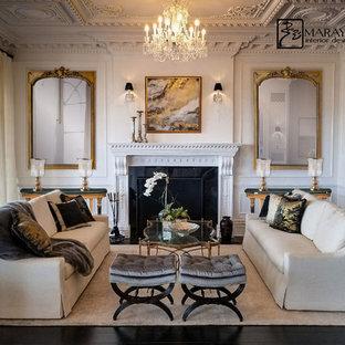 巨大なトラディショナルスタイルのおしゃれなLDK (白い壁、濃色無垢フローリング、標準型暖炉、木材の暖炉まわり、白い床) の写真