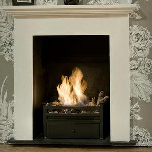 ロンドンの中サイズのトラディショナルスタイルのおしゃれなLDK (薪ストーブ、木材の暖炉まわり) の写真