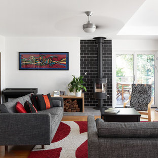 Photo of an eclectic formal enclosed living room in Canberra - Queanbeyan with white walls, medium hardwood floors, a wood stove, a metal fireplace surround, no tv and brown floor.