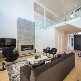 Immagine di un soggiorno design di medie dimensioni e stile loft con pareti bianche, parquet chiaro, camino sospeso, cornice del camino piastrellata e TV a parete