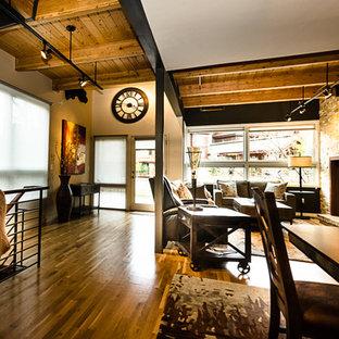 Ispirazione per un soggiorno moderno di medie dimensioni e stile loft con pareti beige, pavimento in legno massello medio, camino classico, cornice del camino in pietra e TV a parete