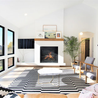 Photo of a large scandinavian formal open plan living room in Grand Rapids with white walls, light hardwood flooring, a standard fireplace, a plastered fireplace surround, a wall mounted tv and beige floors.