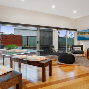 This is an example of a small nautical open plan living room in Central Coast with white walls, bamboo flooring and no fireplace.