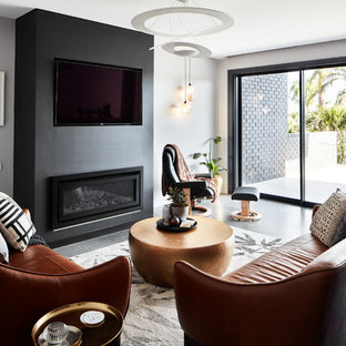 Photo of a contemporary living room in Sydney with grey walls, a wall-mounted tv, concrete floors, a ribbon fireplace and red floor.