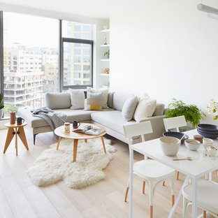 Inspiration for a small scandinavian open plan living room in Seattle with white walls, light hardwood flooring, a two-sided fireplace, a stone fireplace surround and beige floors.