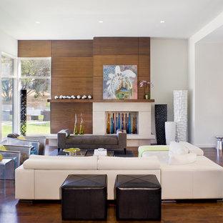 Cette photo montre un grand salon tendance ouvert avec un mur blanc, une salle de réception, un sol en bois brun, une cheminée standard, un manteau de cheminée en pierre, aucun téléviseur et un sol marron.