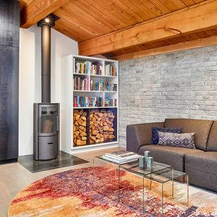 Idee per un soggiorno contemporaneo con stufa a legna, TV nascosta, pareti multicolore, parquet chiaro e cornice del camino in metallo