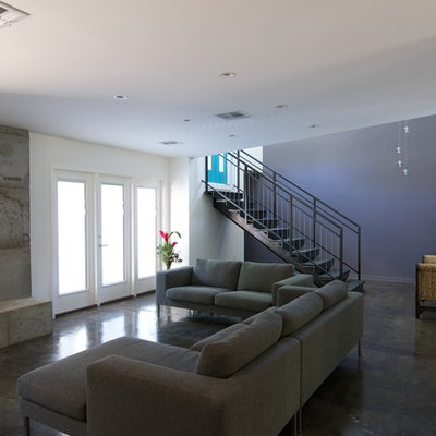 Example of a trendy living room design in Houston with blue walls and a concrete fireplace