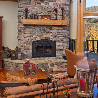 Foto di un soggiorno american style di medie dimensioni e aperto con pareti beige, pavimento in legno massello medio, camino ad angolo e cornice del camino in pietra