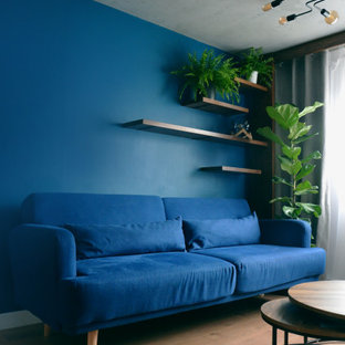 Ispirazione per un piccolo soggiorno industriale chiuso con sala formale, pareti blu, pavimento in laminato, camino bifacciale, cornice del camino in cemento, TV a parete, pavimento marrone e soffitto ribassato