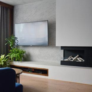 Foto de salón para visitas cerrado, urbano, pequeño, con paredes azules, suelo laminado, chimenea de doble cara, marco de chimenea de yeso, televisor colgado en la pared y suelo marrón