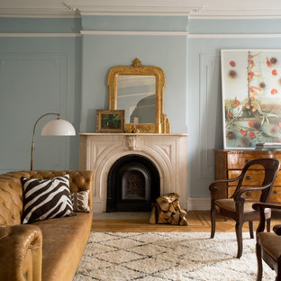 Inspiration for a timeless medium tone wood floor and brown floor living room remodel in New York with blue walls and a standard fireplace
