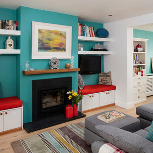 Medium sized coastal open plan living room in Dublin with blue walls, light hardwood flooring, a standard fireplace, a stone fireplace surround and a wall mounted tv.