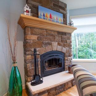 グランドラピッズのビーチスタイルのおしゃれなLDK (青い壁、淡色無垢フローリング、標準型暖炉、石材の暖炉まわり、壁掛け型テレビ) の写真